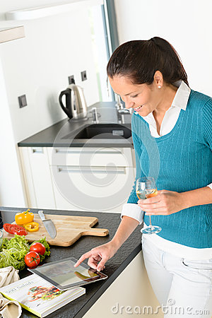 Woman searching recipe tablet kitchen vegetables book