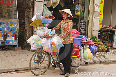 Woman selling brooms and plastic objects Editorial Photography