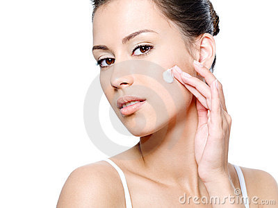 Woman with sensual look applying cream on her face