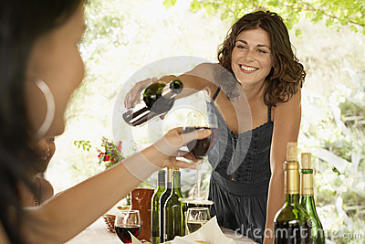 Woman Serving Red Wine To Female Friend In Party