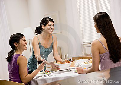 Woman serving spaghetti to friends