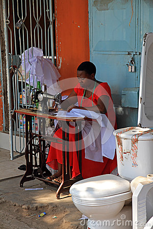 Woman Sewing on the Street beside a Toilet Editorial Stock Image