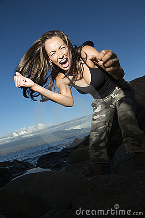 Woman shaking fists by ocean.