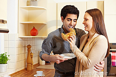 Woman sharing croissant with man