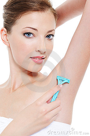 Woman shaving armpit with razor