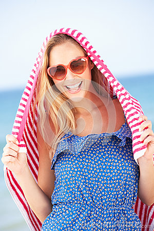 Woman Sheltering From Sun On Beach Holiday