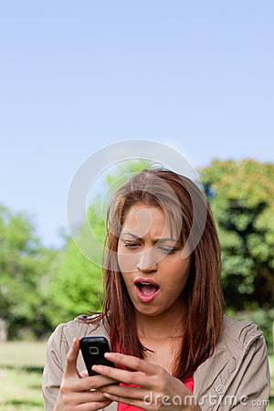 Woman with a shocked while reading a text message