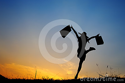 Woman and shopping bags jump in sunset silhouette