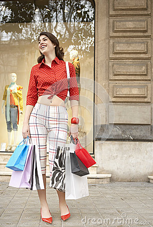 Woman with Shopping Bags Smiling at Store