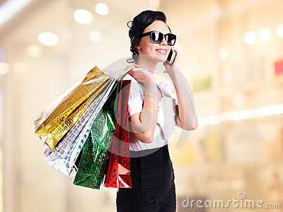 Woman with shopping bags talking on the mobile.