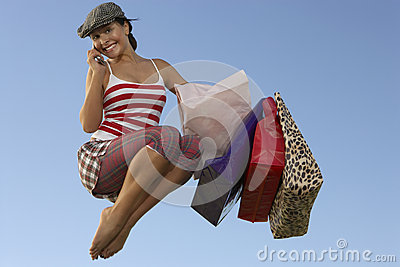 Woman With Shopping Bags Using Cell Phone In Midair