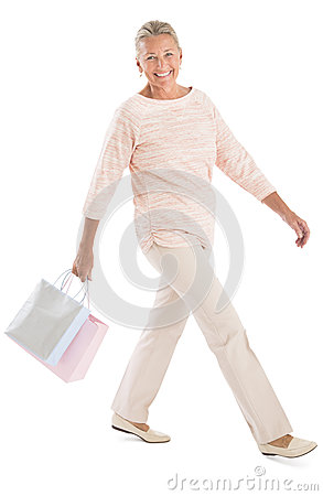 Woman With Shopping Bags Walking Against White Background