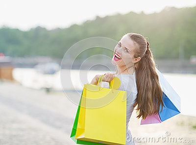 Woman with shopping bags walking embankment