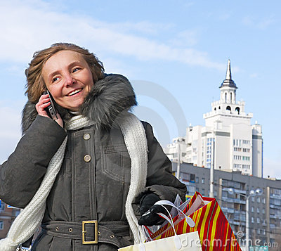 Woman with shopping and a telephone in the city