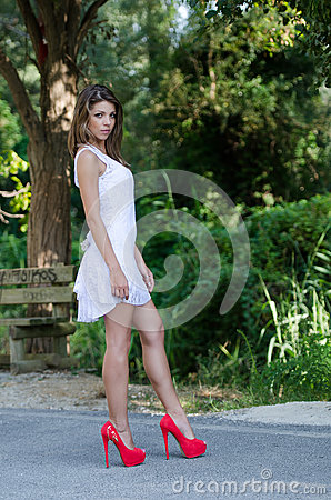 Ways to Date women - How to Be Great and Passionate With a Woman woman short white dress lush vegetation as background side view slim good looking shapely long legs bolt red 60496174