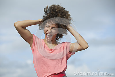 Woman shouting with hand in hair