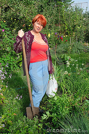 Woman with shovel in garden