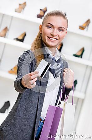 Woman showing credit card in footwear shop