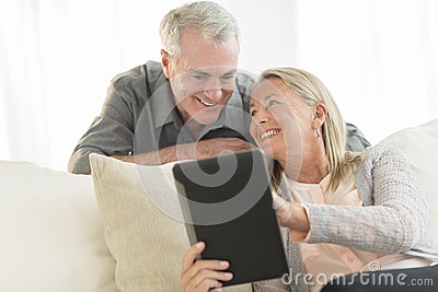 Woman Showing Digital Tablet To Man At Home