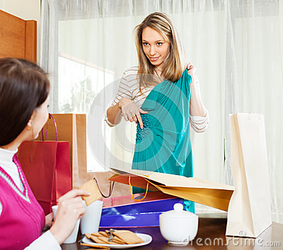 Woman showing new green dress to girlfriend
