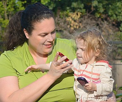 Woman shows cell phone to little girl