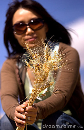 Woman shows stalks of wheat.