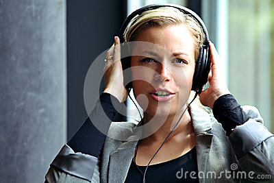 Woman singing along to music on headphones