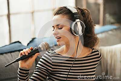 Woman singing with microphone in loft