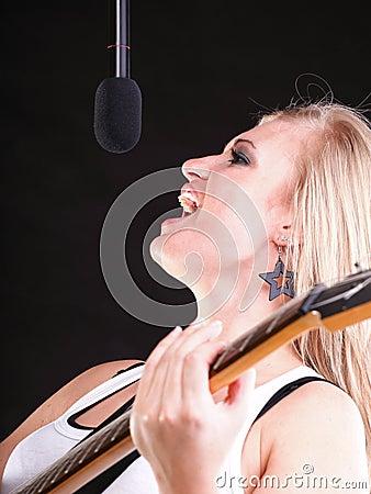 Woman singing rock song microphone headphones