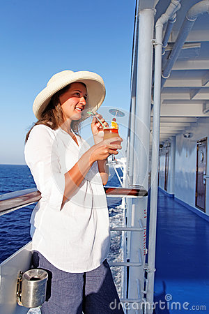 A woman sipping a cocktail happy traveling