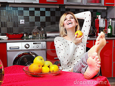 Woman sit in the kitchen with fruit