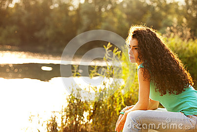 Woman sit by lake