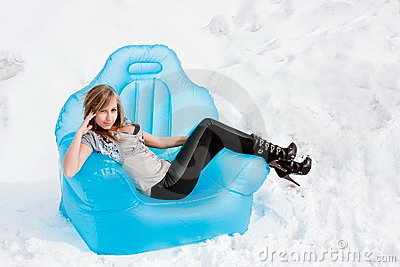 Woman sits in an arm-chair outside in winter