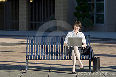 Woman Sits on a Bench with her Laptop - Horizontal