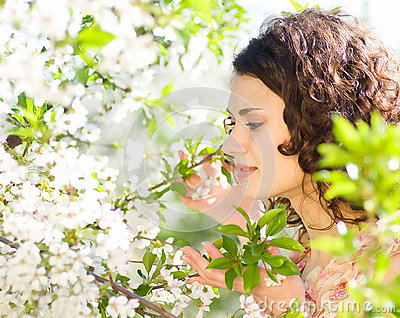 Woman sits on a chair in a spring garden