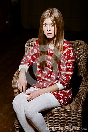 Woman sits in a chair wearing a sweater with the r