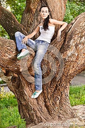 Woman sits on huge tree i