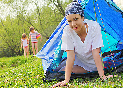 Woman sits inside tent, kids game on lawn