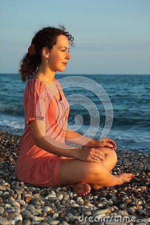 Woman sits and meditation ashore of sea