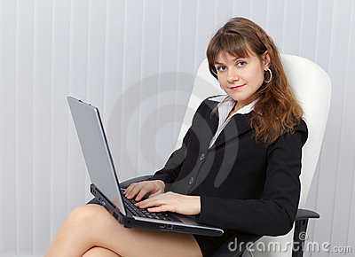 Woman sits in office armchair with laptop
