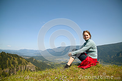 Woman sits at the top of a cliff