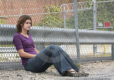 Woman sitting against fence