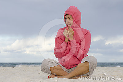 Woman sitting at beach in cold autumn weather