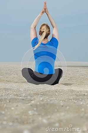 Woman sitting at beach with hands up in yoga position
