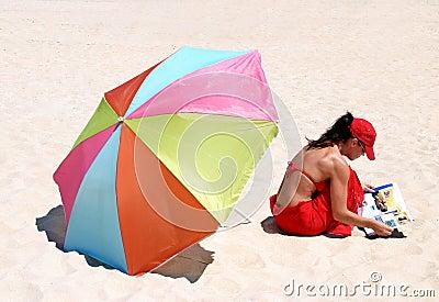 Woman sitting on beach reading
