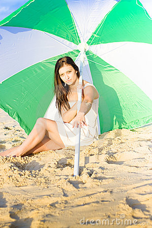 Woman Sitting On Beach With Umbrella Or Parasol
