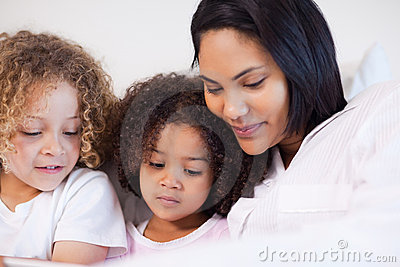 Woman sitting on the bed with her daughters