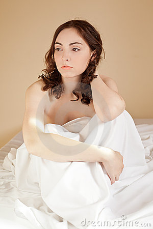 Woman sitting in bed on the white bed-clothes