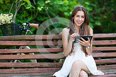 Woman sitting on bench with digital tablet