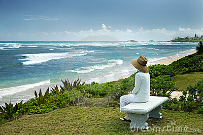 A Woman Sitting on a Bench Overlooking the Sea